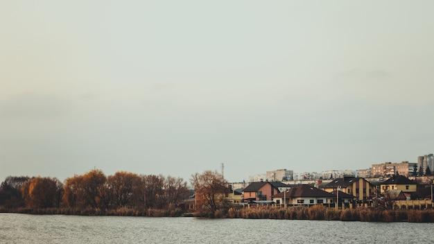 Helder meer omgeven door herfstbomen en huizen