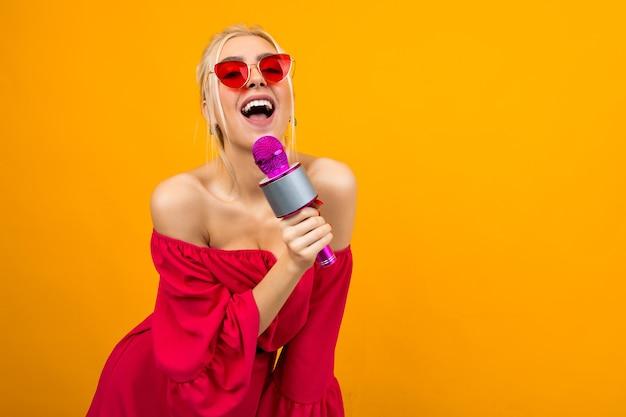 Helder meisje in een rode jurk met blote schouders zingt met een microfoon
