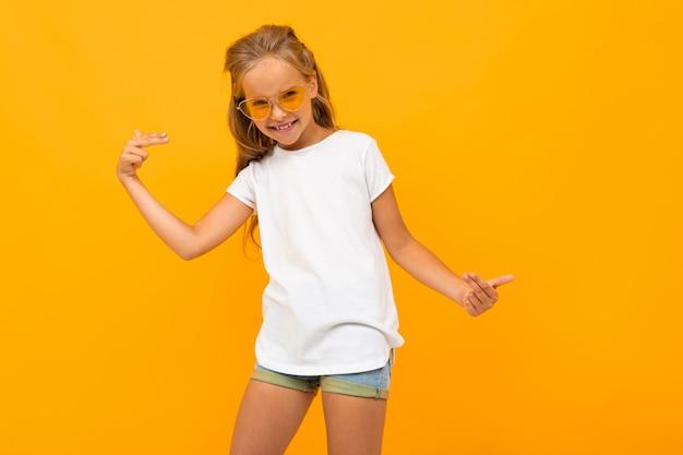 Helder meisje in zonnebril in een wit t-shirt op een gele muur