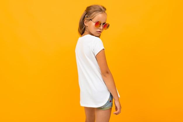 Helder meisje in zonnebril in een wit t-shirt staat terug op een gele muur