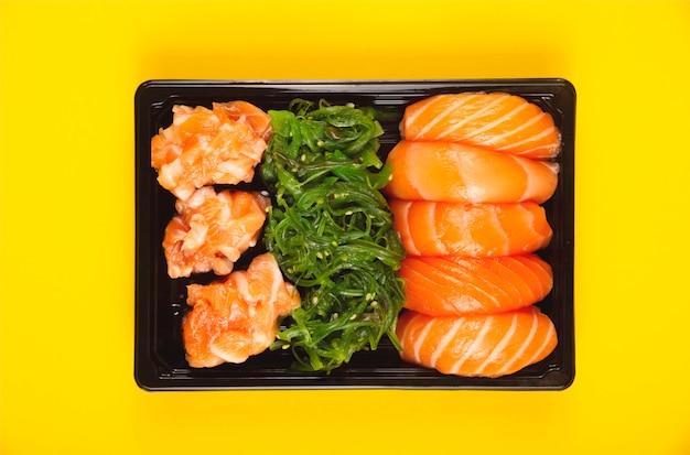 Helder mooie sushi met verse vis, kaviaar en chuka op geel