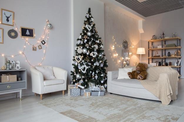 Helder nieuwjaarsvieringsdecor. lichte kamer met kerstinterieur, kerstboom versierd met knipperende slinger en ballen