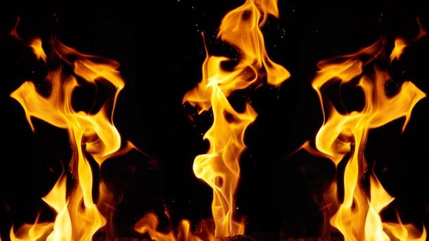 Helder oranje en gele vlammen met vonken op zwarte achtergrond