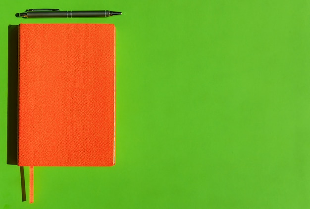 Helder oranje kladblok en stijlvolle grijze pen op groene achtergrond