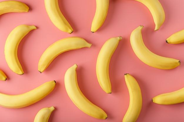 Helder patroon van gele bananen op een roze achtergrond. uitzicht van boven. plat leggen. fruit patronen