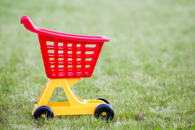 Helder plastic kleurrijk boodschappenwagentjestuk speelgoed in openlucht op zonnige de zomerdag