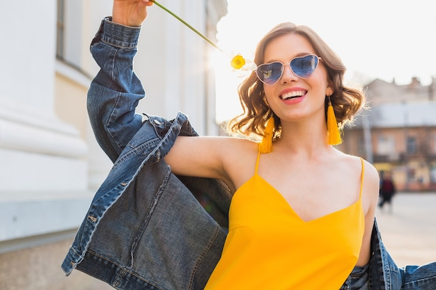 Helder portret van mooie vrouw met bloem, gele jurk, denim jasje, hipster stijl, zomer modetrend, glimlach, trendy zonnebril