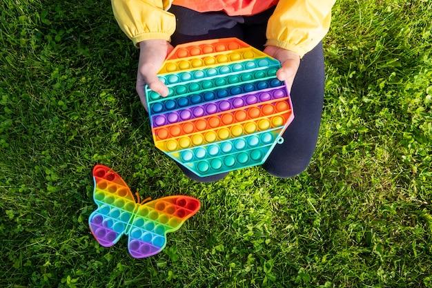 Helder regenboog speelgoed anti-stressprogramma voor kinderen en volwassenen op een kleurrijke achtergrond. flexibel zintuiglijk antistress speelgoed - popit.