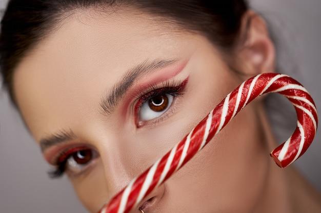 Helder rood oog make-up vrouw close-up met karamel in haar handen, mooie zelfs wenkbrauwen en lange wimpers
