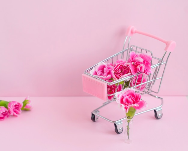 Helder roze anjers bloemen in een kar op een roze achtergrond, het concept van het leveren van bloemen en planten bij u thuis