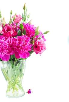 Helder roze pioen en eustoma bloemen boeket in glazen vaas close-up geïsoleerd op een witte achtergrond