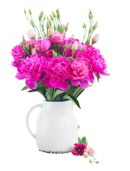 Helder roze pioen en eustoma bloemen boeket in pot geïsoleerd op wit