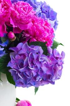 Helder roze pioenroos en blauwe hortensia verse bloemen boeket close-up geïsoleerd op wit