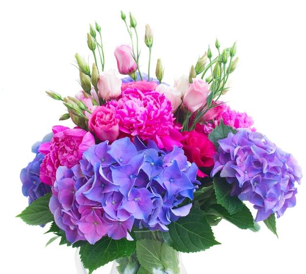 Helder roze pioenroos, eustoma en blauwe hortensia bloemen boeket close-up geïsoleerd op wit