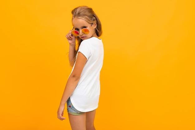 Helder schattig meisje in glazen in een t-shirt met een indeling op een oranje muur
