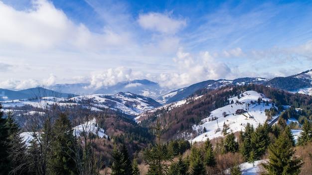 Helder schilderachtig landschap van bergen en heuvels begroeid met bomen en struiken op een zonnige ijzige winterdag