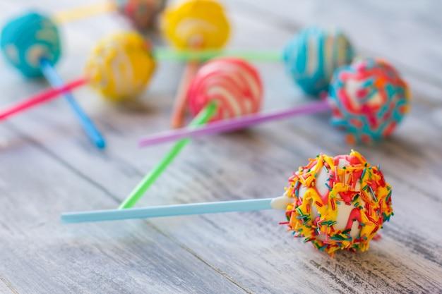 Helder snoep op een stokje. cakepop met slagroom. hoe maak je kinderen gelukkiger. witte chocolade en crème vulling.