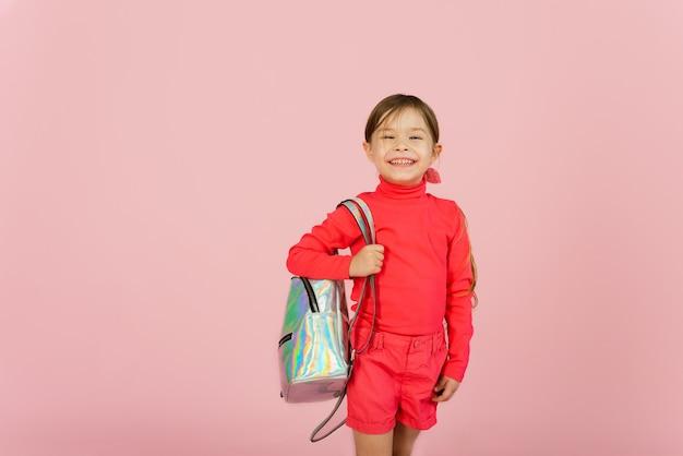 Helder tienermeisje met een kort kapsel en roze make-up op een rode achtergrond