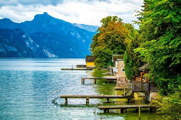 Helder uitzicht op bos en berthes bij kleine huizen aan het brede traunsee-meer in gmunden