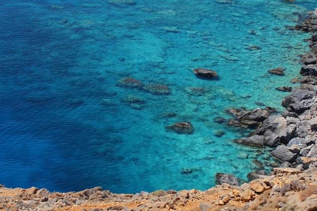 Helder water zee in de buurt van rotsen overdag