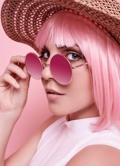 Helder zomerportret van een positief, schitterend meisje met roze haar, zonnebril en een gevlechte hoed op kleurrijke studio