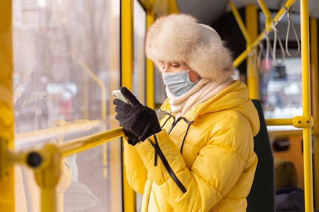 Helder zonnig portret van een jonge vrouw in warme kleren in een stadsbus op een winterse dag met een mobiele telefoon in haar hand