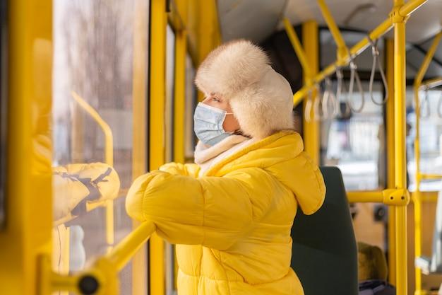 Helder zonnig portret van een jonge vrouw in warme kleren in een stadsbus op een winterse dag