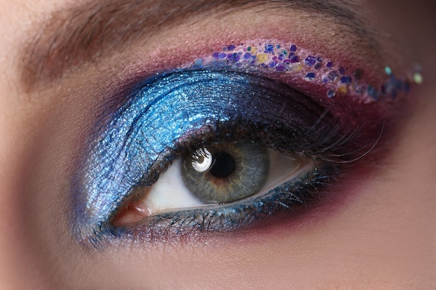 Helderblauwe avond ooglid make-up met veelkleurige sparkles artist make-up concept