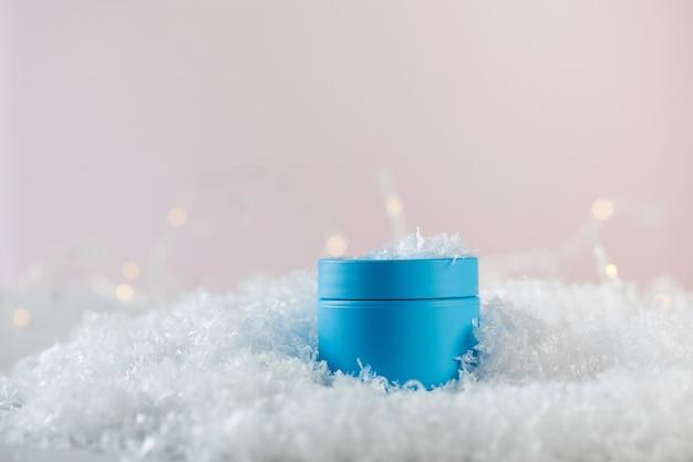Helderblauwe lege pot met winterbeschermend cosmetisch product in kunstmatige sneeuw
