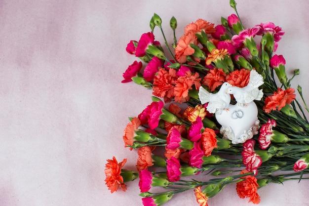 Heldere anjers op een roze achtergrond en twee witte duiven - huwelijksachtergrond