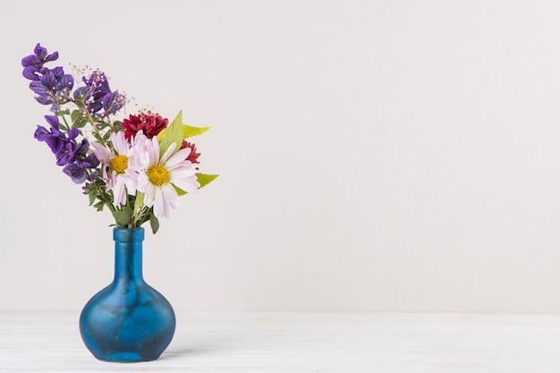 Heldere bloemen in blauwe vaas op tafel