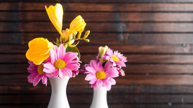 Heldere bloemen in twee vazen