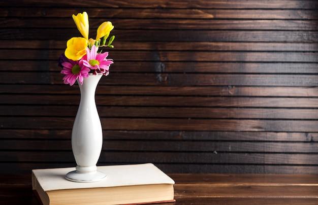 Heldere bloemen in vaas op boek