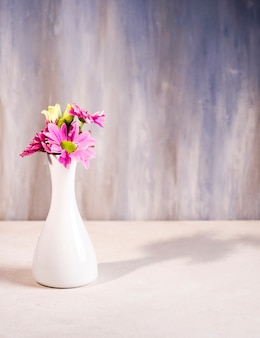 Heldere bloemen in witte vaas op tafel