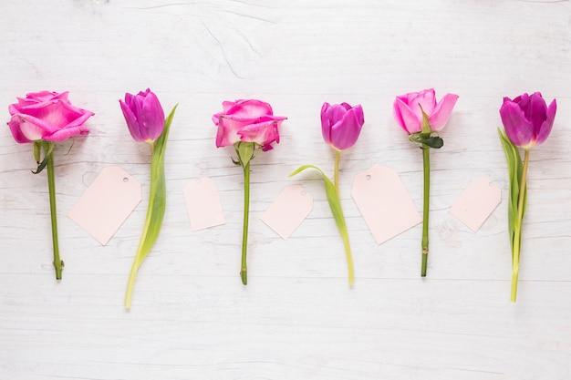 Heldere bloemen met kleine papieren op tafel
