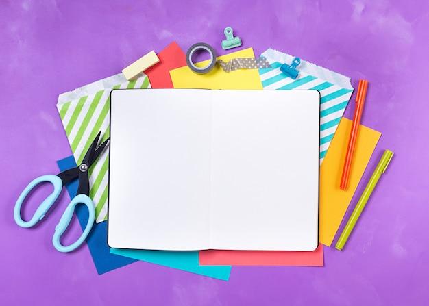 Heldere bureaulevering, schoolkantoorbehoeften, witte blocnote op de lijst, purpere achtergrond. terug naar school-concept. bovenaanzicht. ruimte kopiëren.