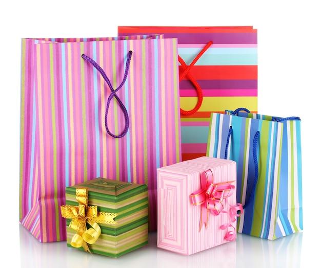 Heldere cadeautassen en geschenken op wit wordt geïsoleerd