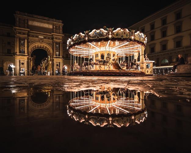 Heldere carrousel met reflectie 's nachts