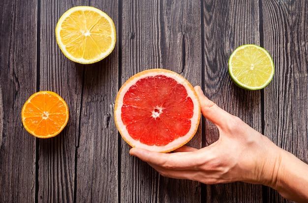Heldere citrusvruchten op een houten donkere achtergrond.