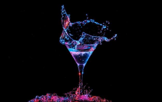 Heldere cocktail met citroen in glas en opspattend water op donkere achtergrond