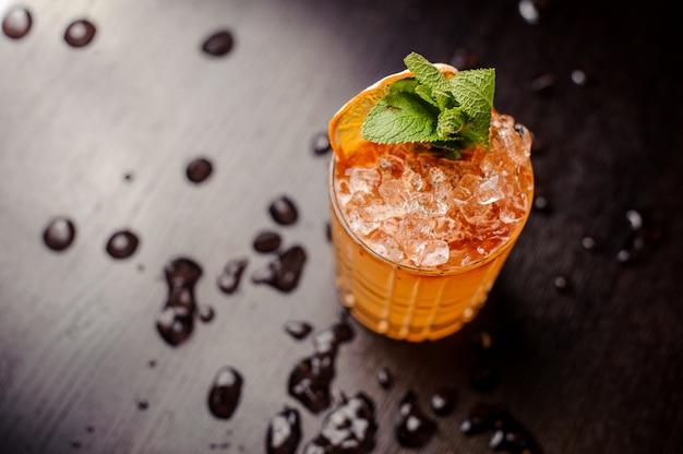 Heldere cocktail met muntblaadjes en een schijfje sinaasappel
