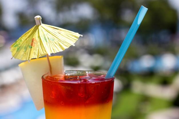 Heldere cocktail met paraplu op de achtergrond van het zwembad