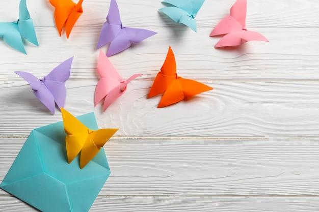 Heldere coloful papieren vlinders vliegen uit de envelop.