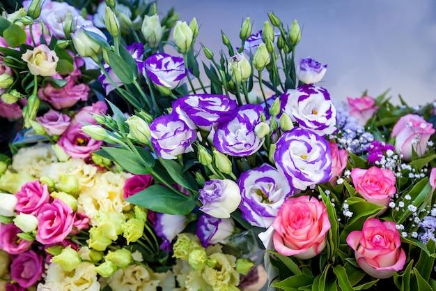 Heldere decoraties van bloemen op tafel tijdens een huwelijksceremonie. een groep kleurrijke rode en violette bloemen.