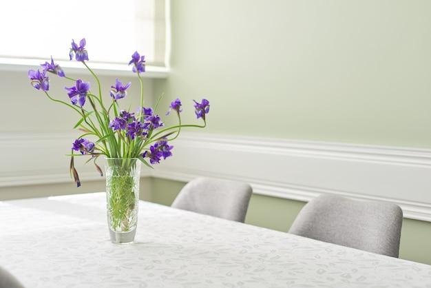 Heldere eetkamer interieur, tafel en stoelen in de buurt van raam, boeket van paarse irissen in vaas, wit tafelkleed ruimte, kopie ruimte