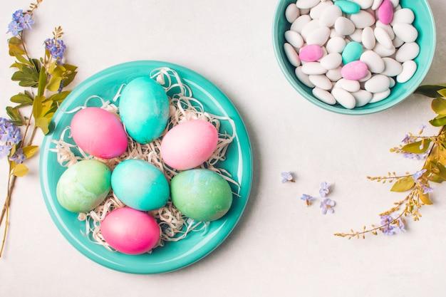 Heldere eieren op plaat dichtbij kleine stenen in kom en bloemtwijgen