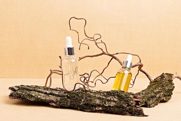 Heldere en amberkleurige serums in glazen flessen met houten natuurelementen. natuurlijke eco-vriendelijke schoonheidsproducten concept. detailopname