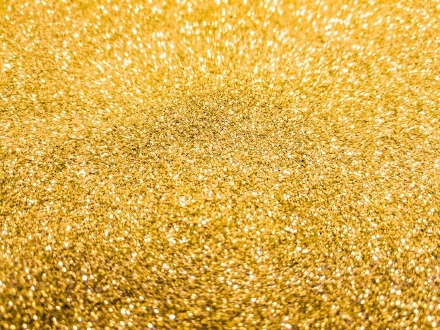 Heldere en fonkelende bokeh achtergrond. geel goud - vage verlichting van glittertextuur.