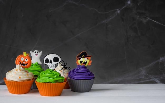 Heldere enge halloween cupcakes op een donkere achtergrond met spinnenwebben. gekleurde crème en decor.