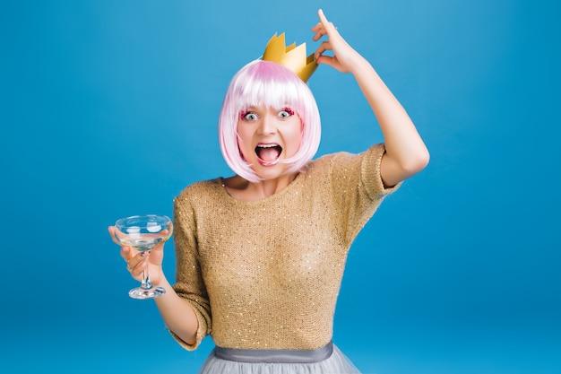 Heldere feesttijd van grappige jonge vrouw met champagne, gouden kroon op hoofd die pret heeft. knip roze haar, uiting van geluk, verbaasd, nieuwjaarsfeest, carnaval.